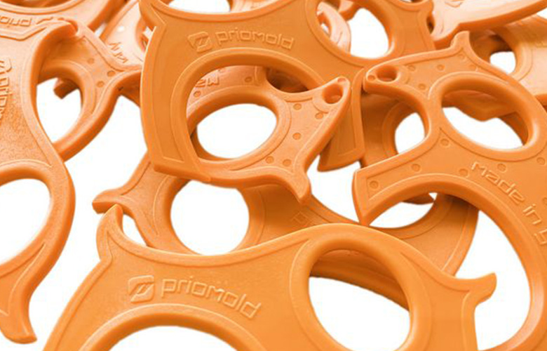 Orange injection moulded parts with Priomold inscription
